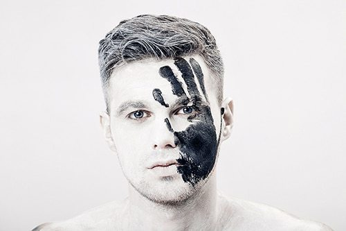 Young man with black hand print on his white face. Close up Portrait.  Professional Fashion Makeup. fantasy art  makeup