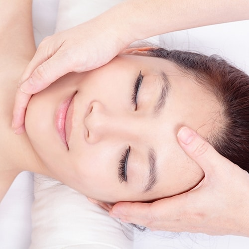 """Beautiful asian woman enjoy receiving face and head massage at spa center, view from high angleModel:"""